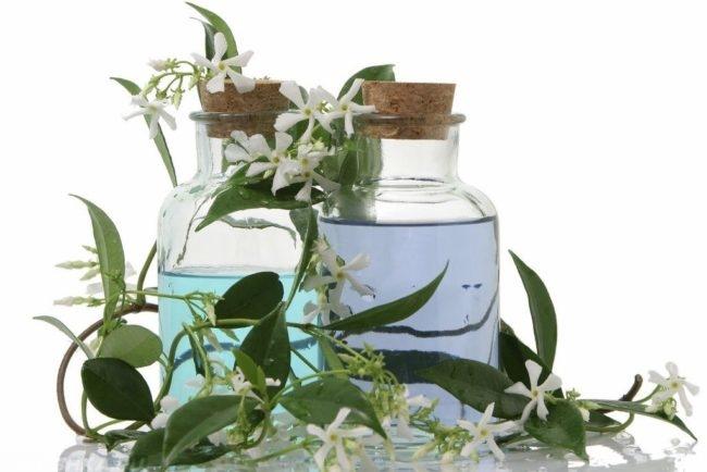 Эфирное масло с цветами жасмина в стеклянных бутылках