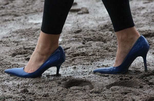 Хозяйка кошки идёт в туфлях по грязи
