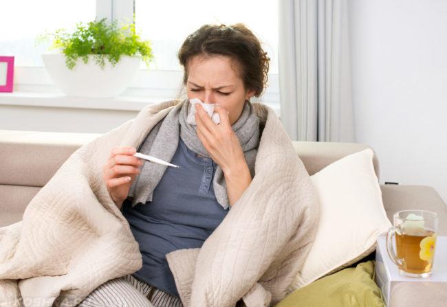 Женщина чихает и измеряет свою температуру тела с помощью градусника