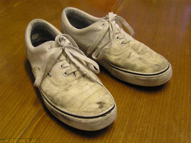 Зашнурованные грязные ботинки на деревянном полу в квартире