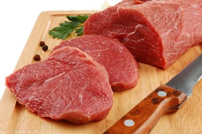 Кусок красного разрезанного ножом мяса на доске
