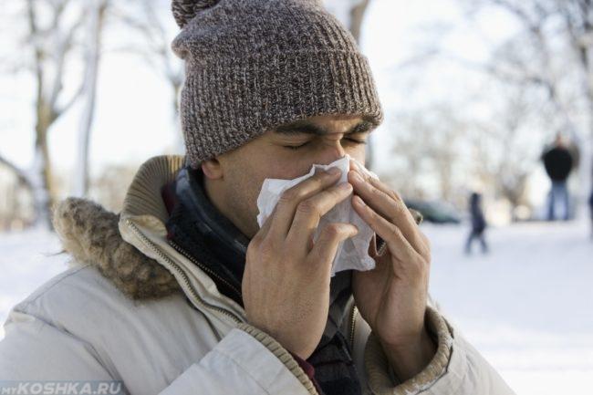 Заболевший мужчина на холоде чихает в белый платок