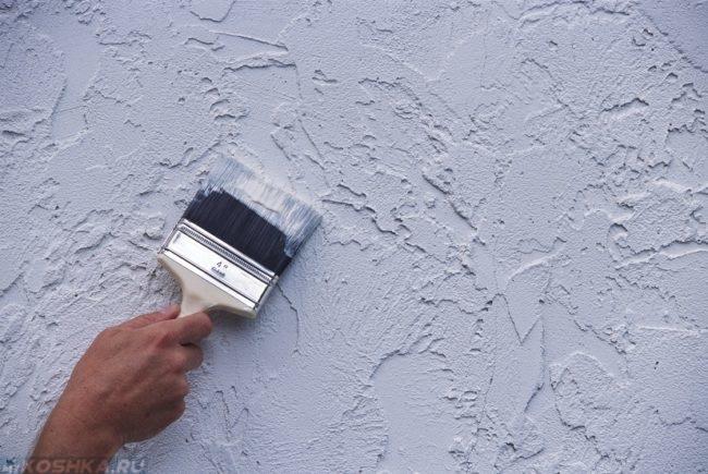 Нанесение серых жидких обоев кистью на стену