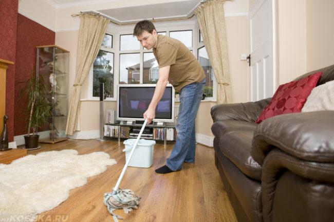 Мужчина в коричневой футболке с шваброй в руках моет пол в квартире