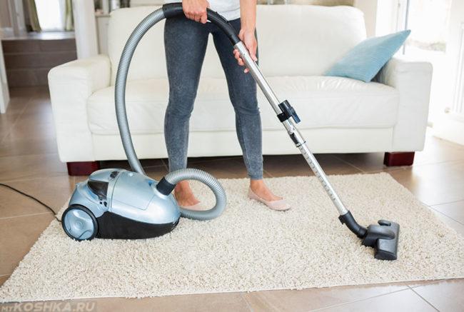 Женщина в синих джинсах пылесосит белый ковер в комнате
