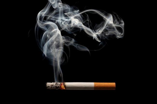 Сигарета и дым на черном фоне