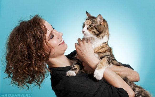 Женщина в черной кофте держит на руках коричневую полосатую кошку