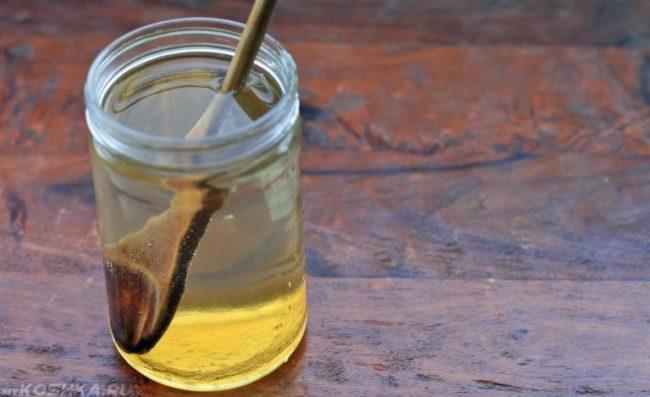 Водный раствор мёда в прозрачной банке с деревянной ложкой