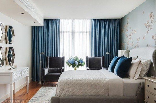 Синие шторы в спальне с белой кроватью