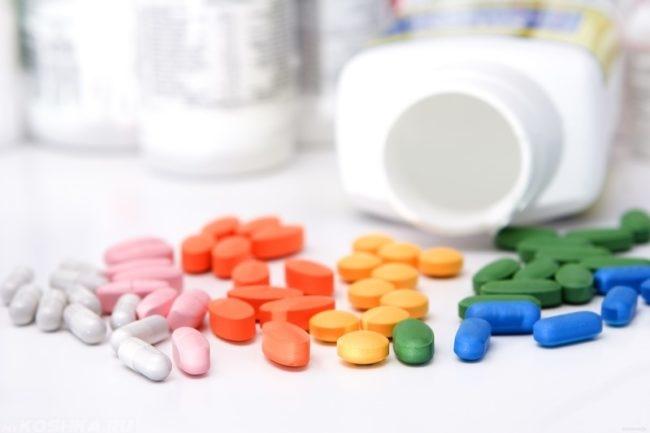 Разноцветные витамины и пустая белая баночка