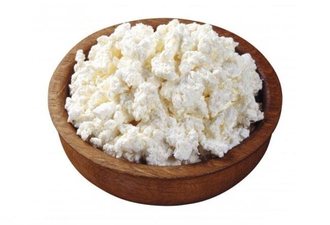 Белый творог в деревянной миске