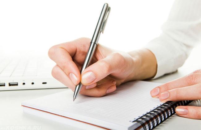 Блокнот на столе и ручка в руке