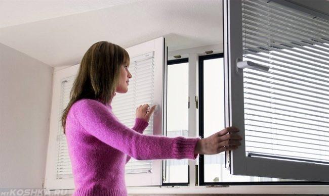Женщина открывающая окно