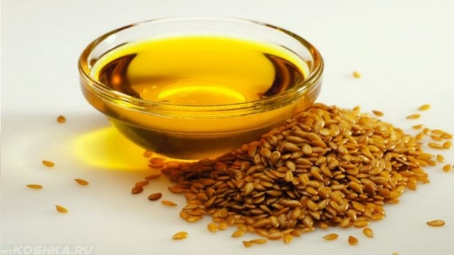 Льняное масло в прозрачной чашке и семена