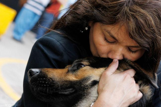 Женщина обнимающая собаку