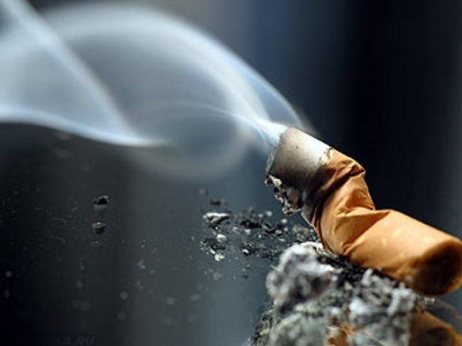 Дымящая сигарета на сером фоне