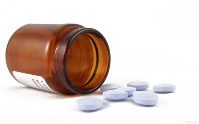 Белые таблетки и коричневая баночка на белом фоне