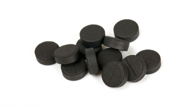 Таблетки активированного угля на белом фоне