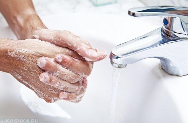 Мытьё рук под краном над раковиной с мылом