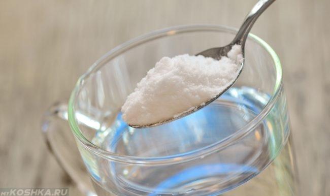 Сода в ложке и стакан с водой