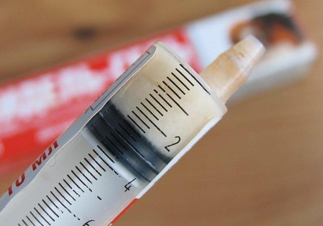 Шприц с мерной шкалой для правильного нанесения лечебной мази на ухо кролика