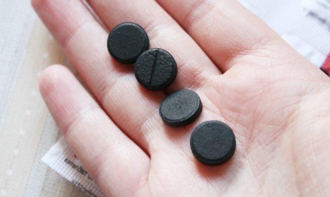 Четыре черные таблетки активированного угля на ладони кроликовода